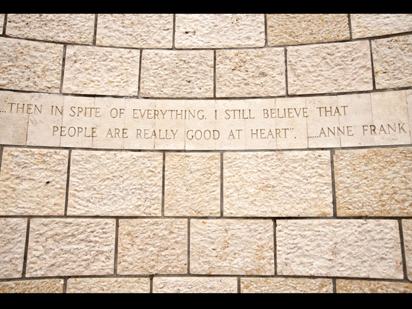 """<strong>Anne Frank's Message</strong><br> The beginning sculpture is framed by a quote from Anne Frank: """"… in spite of everything, I still believe that people are really good at heart."""""""